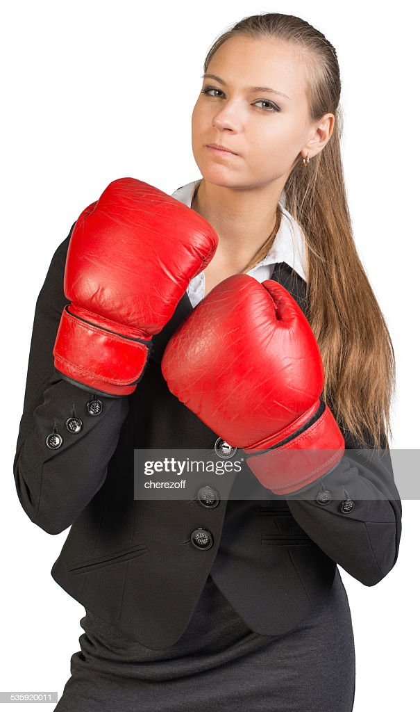 Businesswoman wearing boxing gloves, giving tough look at camera : Stock Photo