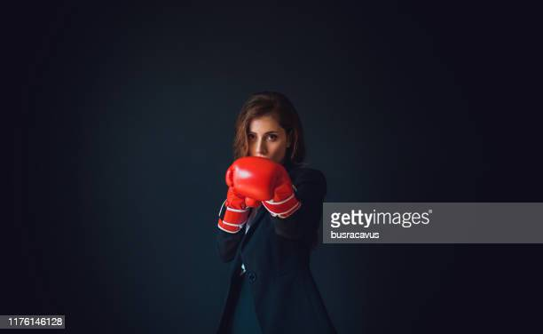 businesswoman wearing boxing gloves - combat sport stock pictures, royalty-free photos & images