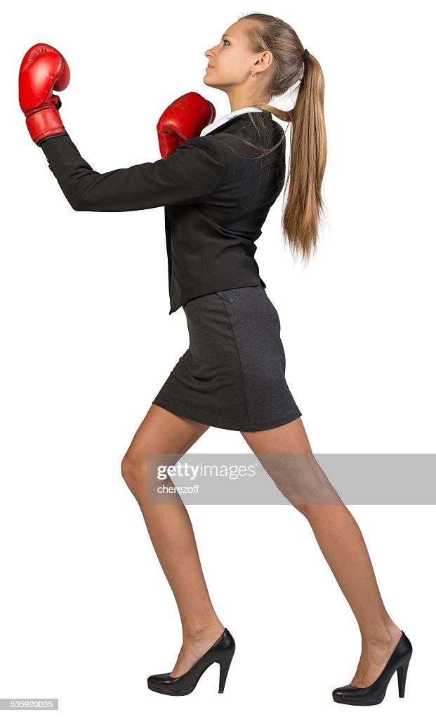 Businesswoman wearing boxing gloves punching : Stock Photo