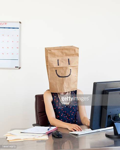 Businesswoman wearing brown bag with smiley face