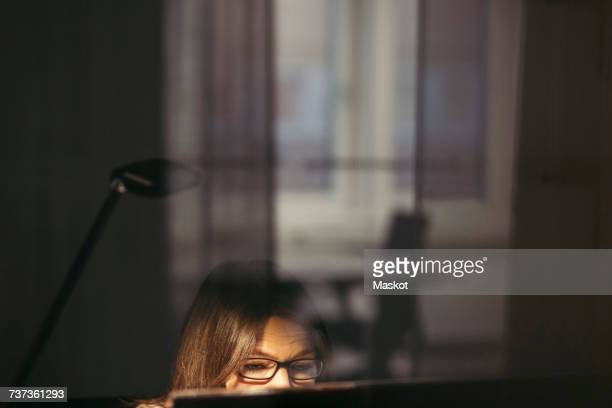 Businesswoman wearing eyeglasses using computer seen through glass at office