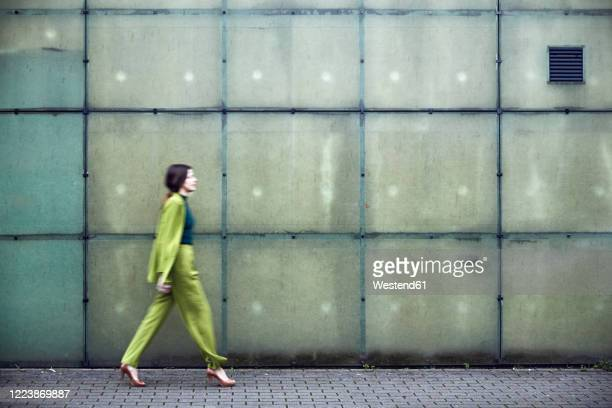 businesswoman wearing green suit passing a wall - pant suit stock pictures, royalty-free photos & images