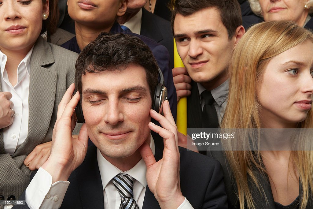 Businesswoman wearing headphones on subway train : Stock Photo