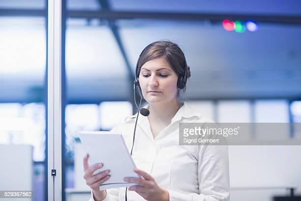 businesswoman wearing headset and reading document, freiburg im breisgau, baden-w��rttemberg, germany - sigrid gombert fotografías e imágenes de stock