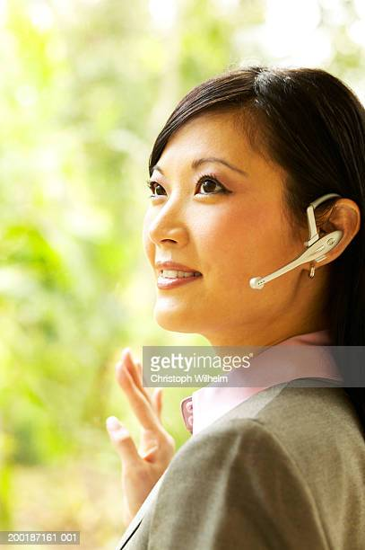 Businesswoman wearing headset, smiling, close-up
