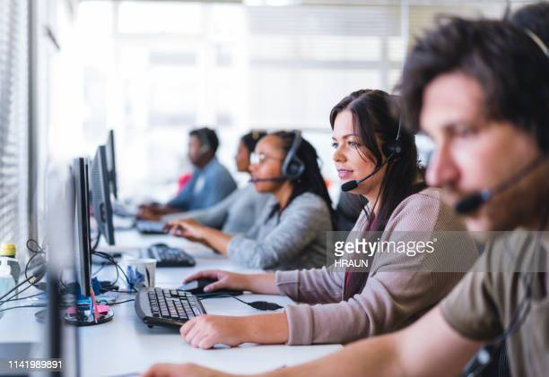 businesswoman wearing headset while using computer - assistance stock pictures, royalty-free photos & images