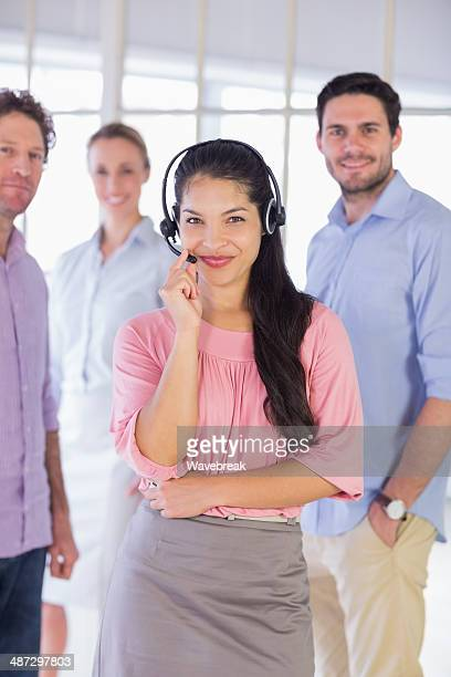 Businesswoman wearing headset with colleagues in office