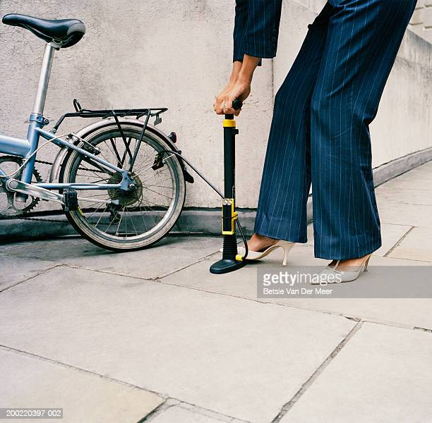 businesswoman wearing high heeled shoes pumping bicycle tyre - air pump stock photos and pictures