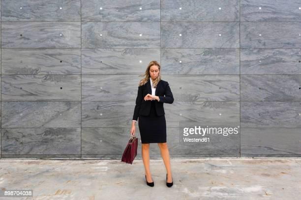 businesswoman wearing ladies' suit checking the time - attaché stockfoto's en -beelden