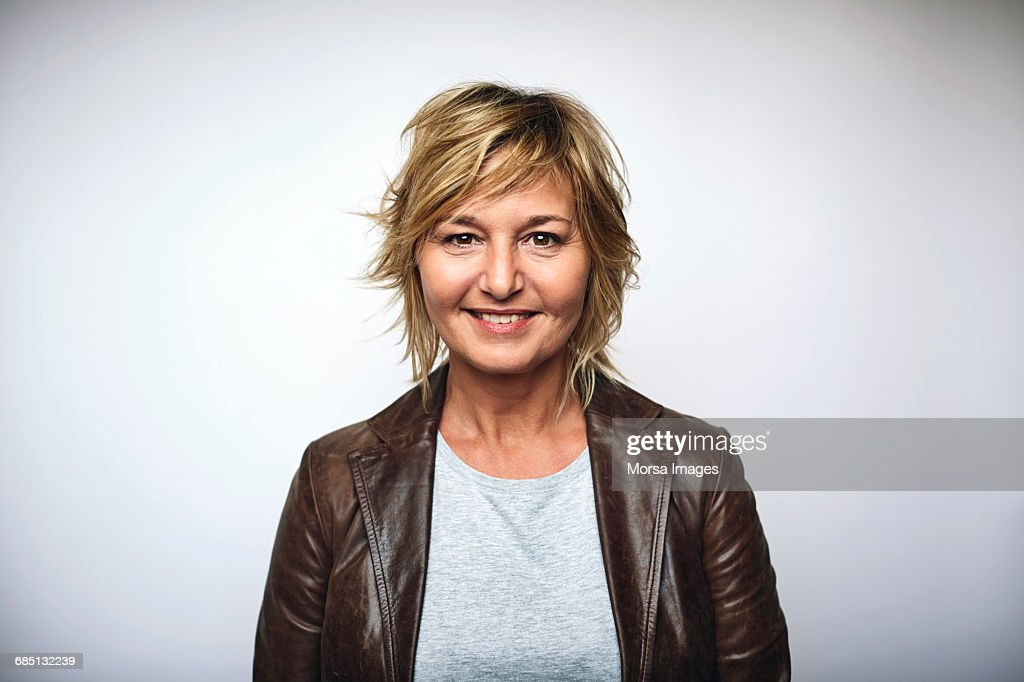 Businesswoman wearing leather jacket over white : Stock Photo