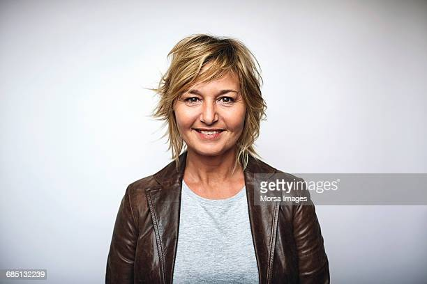 businesswoman wearing leather jacket over white - white background stockfoto's en -beelden