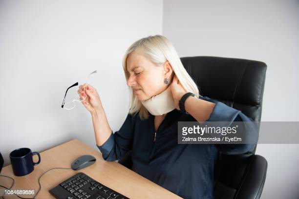 Businesswoman Wearing Neck Brace Suffering From Pain In Office