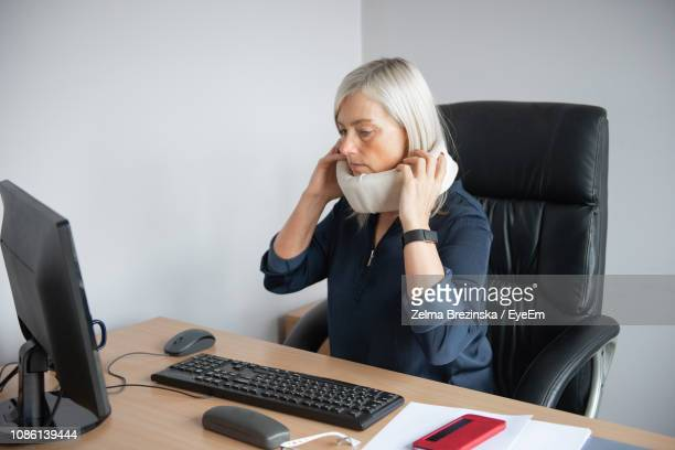 Businesswoman Wearing Neck Brace While Sitting On Chair In Office