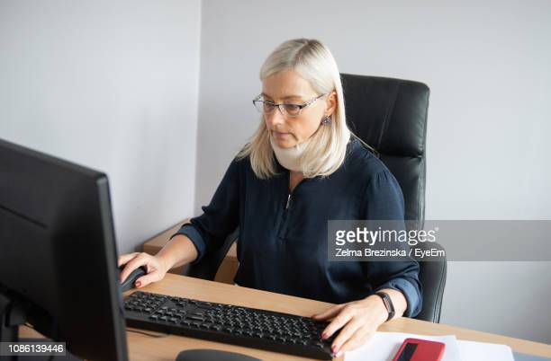 Businesswoman Wearing Neck Brace While Working On Computer In Office