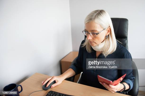 Businesswoman Wearing Neck Brace Working On Computer While Mobile Phone In Office