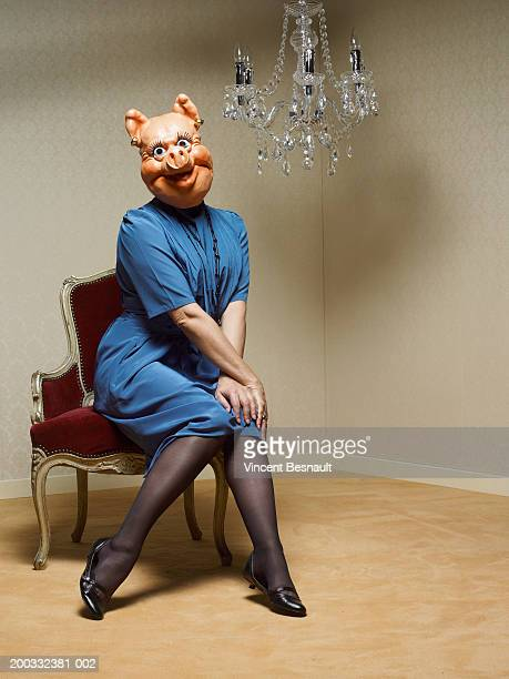 businesswoman wearing pig mask sitting under chandelier, portrait - pantyhose mask stock pictures, royalty-free photos & images