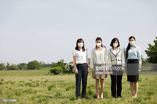 Businesswoman wearing pollution masks in field