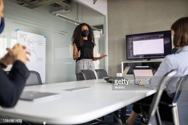 geschäftsfrau trägt schützende gesichtsmaske und erklärt kollegen in präsentation - nicht binäres geschlecht stock-fotos und bilder