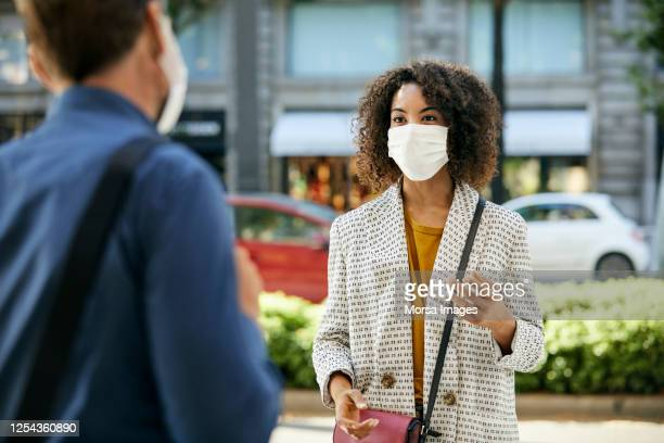 businesswoman wearing protective face mask talking to male coworker during covid-19 pandemic in city - abstand halten infektionsvermeidung stock-fotos und bilder