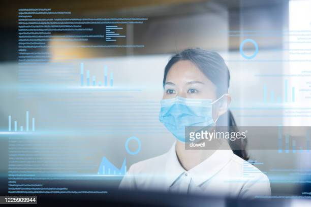businesswoman wearing protective face mask while working - big data health stock pictures, royalty-free photos & images