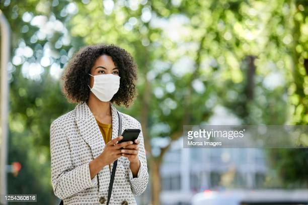 businesswoman wearing protective face mask with smart phone during covid-19 pandemic in city - セレクティブフォーカス ストックフォトと画像
