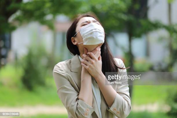Businesswoman wearing protective mask, touching her neck