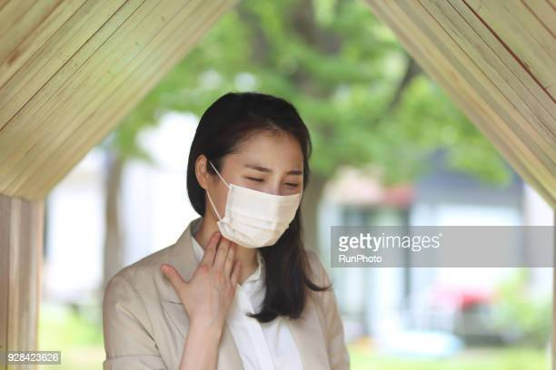 Businesswoman wearing protective mask, touching neck