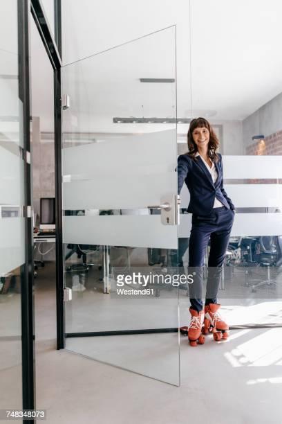 Businesswoman wearing rollerblades, opening glass door