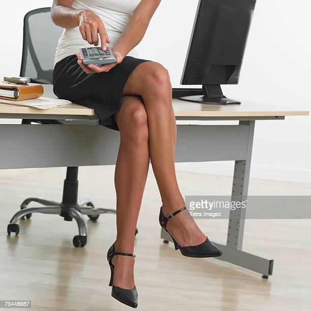 Businesswoman wearing skirt and high heels sitting on desk