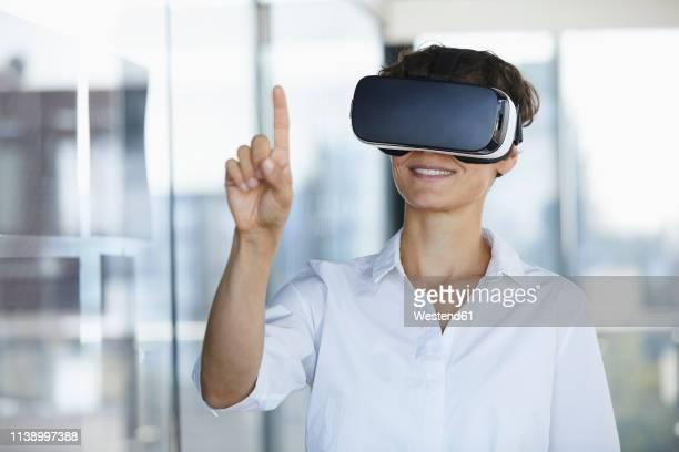 businesswoman wearing vr glasses in office raising her finger - spectacles stock-fotos und bilder