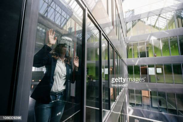 businesswoman wearing vr goggles, standing at window - eskapismus stock-fotos und bilder