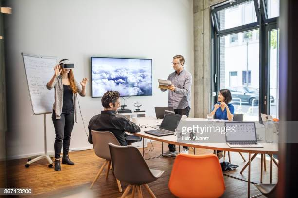 Businesswoman wearing VR headset while giving presentation in board room