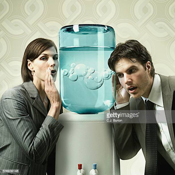 businesswoman whispering into a water cooler - water cooler stock pictures, royalty-free photos & images
