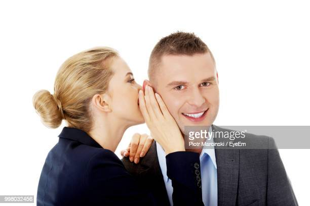 Businesswoman Whispering Secret In Colleague Ear Against White Background