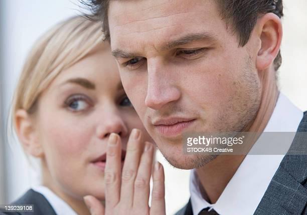 Businesswoman whispering to businessman