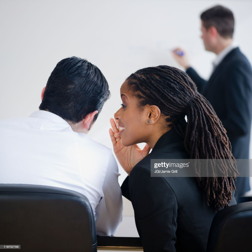 Businesswoman whispering to co-worker in meeting : Stock Photo