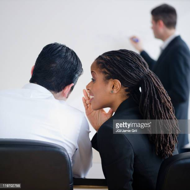Businesswoman whispering to co-worker in meeting