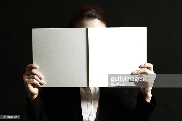 businesswoman with a book over face