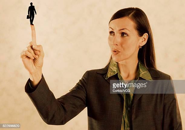 Businesswoman with a Businessman on Her Fingertip