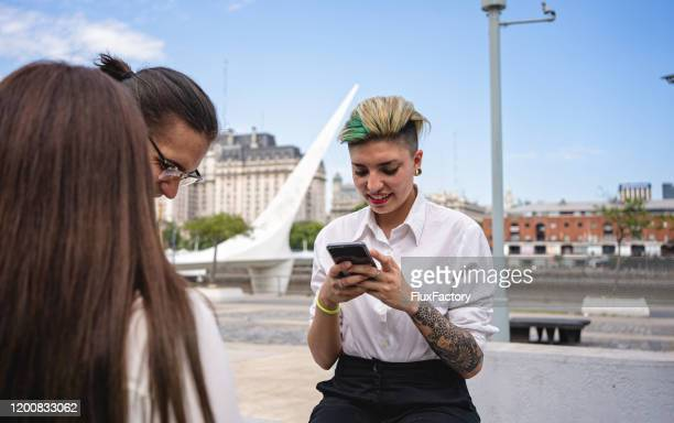 businesswoman with a mobile phone spending time with colleagues outdoors - punk music stock pictures, royalty-free photos & images