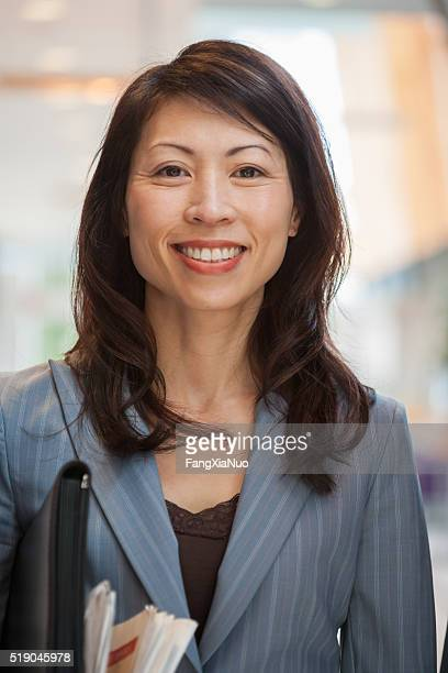 businesswoman with a newspaper and briefcase - east asian culture stock photos and pictures