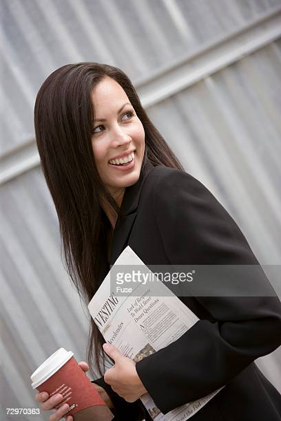 Businesswoman with a newspaper and coffee