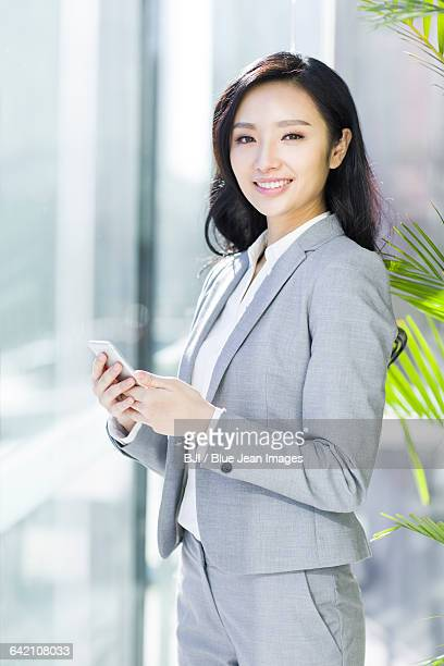 businesswoman with a smart phone - 膝から上の構図 ストックフォトと画像