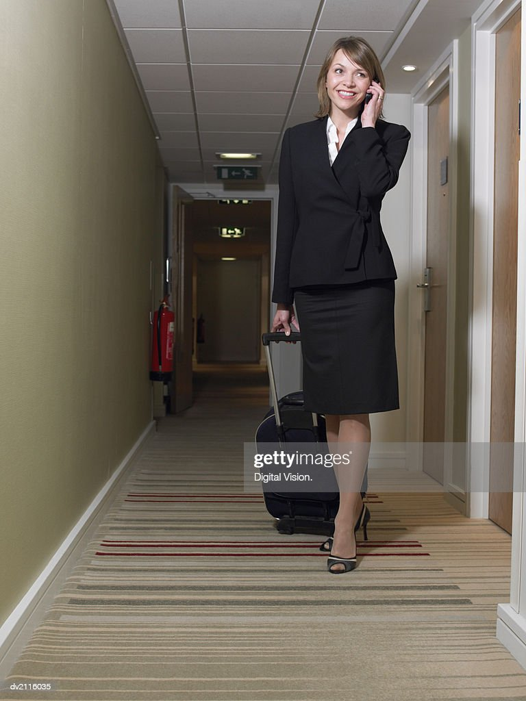 Businesswoman With a Suitcase Using Her Mobile Phone in a Corridor : Stock Photo