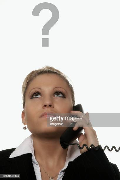 Businesswoman with a telephone in her hand, a question-mark above her head