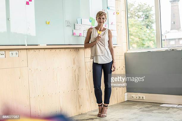 Businesswoman with adhesive notes at whiteboard in modern office