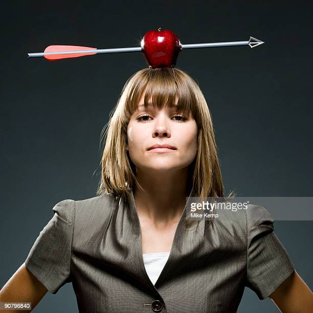 businesswoman with an apple with an arrow through it on her head