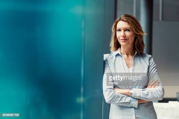 businesswoman with arms crossed at office - waist up stock pictures, royalty-free photos & images