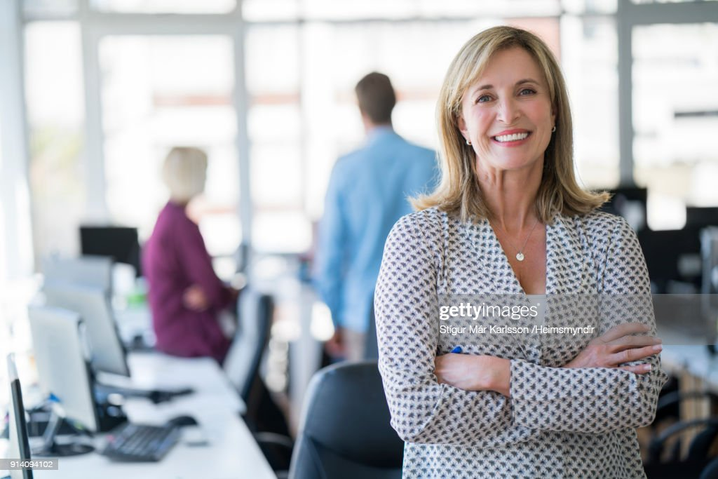 Businesswoman with arms crossed in office : Stock Photo