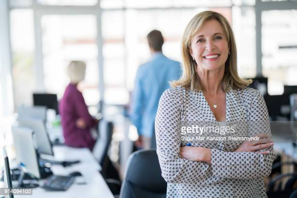 businesswoman with arms crossed in office - smart casual stock pictures, royalty-free photos & images